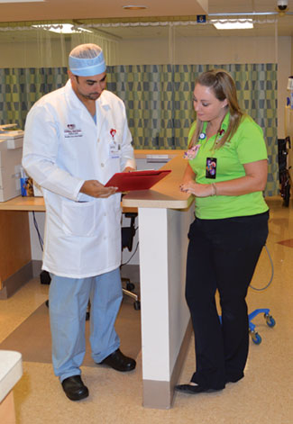 Dr. Carlos Medina looking over a patient's chart with Justine Marty, CCLS Certified Child Life Specialist.